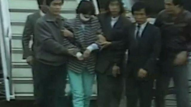 Kim Hyun-hui presa descendo do avião