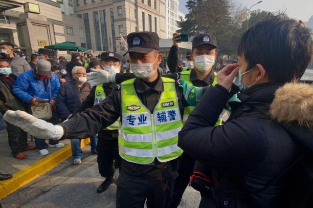 警察阻拦到场的记者和路人拍摄。