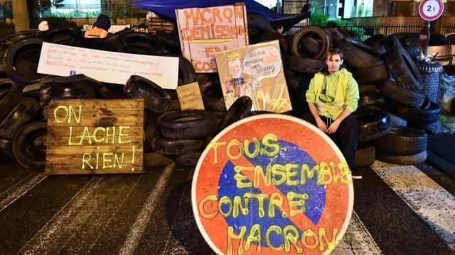 A demonstrator wearing a yellow vest (gilet jaune) sits on a barricade of tires, at the entrance of the Tax Office in Rennes, northwestern France, on December 2, 2018