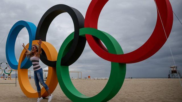 Una mujer posa frente a unos anillos olímpicos en una playa de Río de Janeiro.
