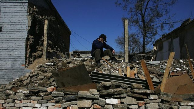 A worker takes a break at a construction site on a street made by demolishing old houses on March 4, 2008 in Beijing, China.