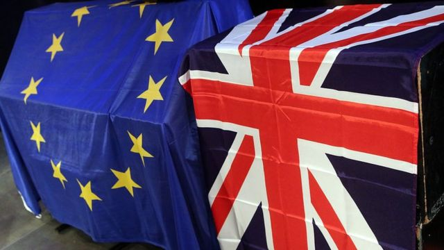 European Union (L) and British Union Jack flags hang at a meeting for British citizens living in Germany to discuss the implications of Great Britain leaving the European Union