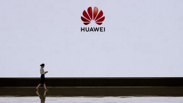 A member of Huawei's reception staff walks in front of a large screen displaying the logo in the foyer of a building used for high profile customer visits and displays at the company's Bantian campus on April 12, 2019 in Shenzhen, China.