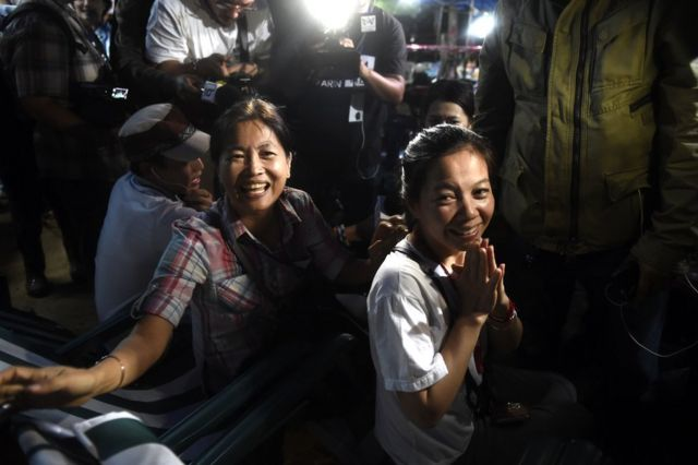 Family members celebrate while camping out near Than Luang cave following news all members of children's football team and their coach were alive in the cave at Khun Nam Nang, 2 July