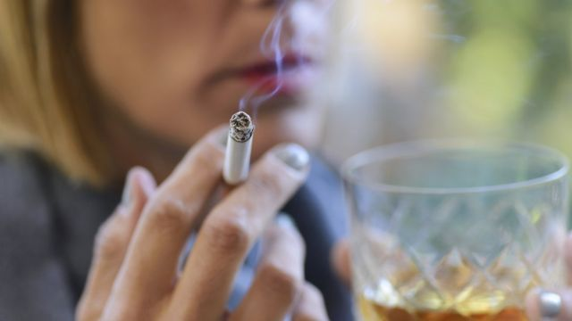 Mujer fumando y bebiendo