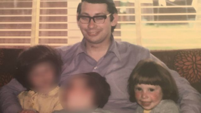 Richard Haynes sits on a couch with his three children including Jeni on the right
