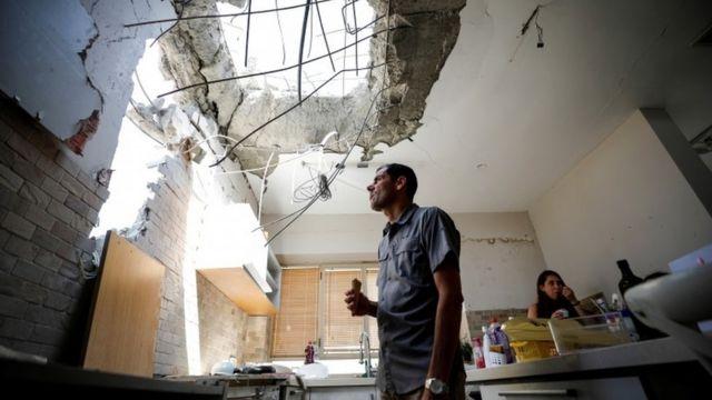 Adi Vaizel, analisa os danos causados à cozinha de sua casa após ser atingida por um foguete lançado da Faixa de Gaza