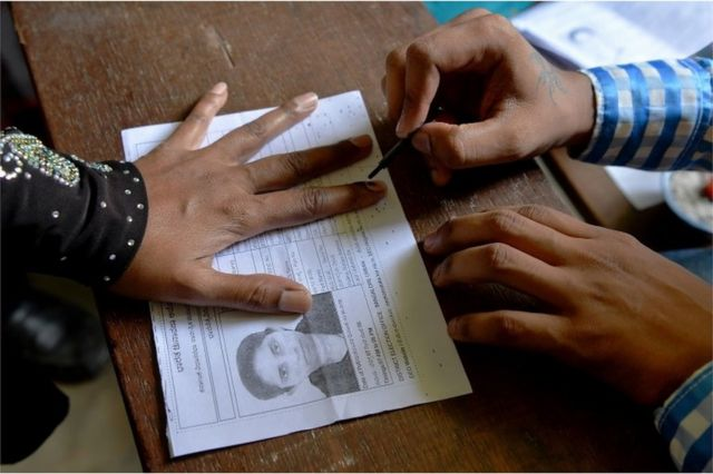 An Indian election official (R) puts indeliable ink on the finger of a voter before she casts her ballot in the Karnataka Legislative Assembly Elections at a polling station in Bangalore on May 12, 2018.