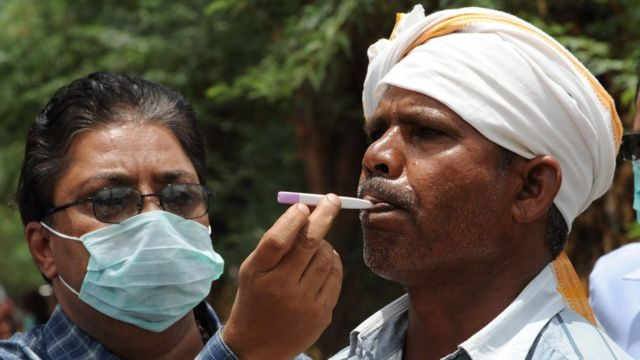 An Indian doctor examines the temperature of a villager