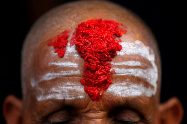 A Hindu priest's forehead is covered with coloured powder and rice used as a blessing, during the sacred thread festival at the Pashupatinath temple in Kathmandu, Nepal 28 July 2017.