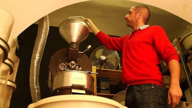 Peter Laszlo pours coffee beans into his roaster in his Budapest cafe, Lumen