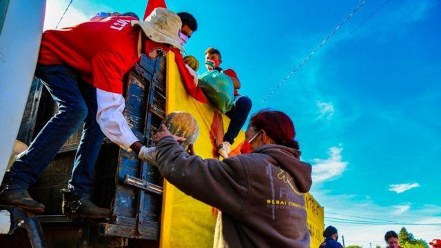 Do alto de um caminhão, um integrante do MST entrega uma abóbora para uma mulher, ambos usam máscaras de proteção contra a covid