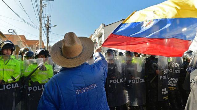 Manifestante en Ecuador agita bandera de su país frente a grupo de policías.