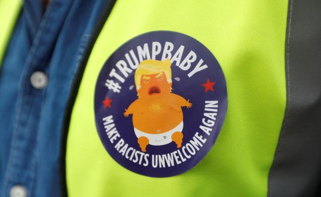 A demonstrator wears a badge depicting US President Donald Trump as a baby