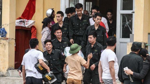 Các cảnh sát được thả (mặc đồng phục sẫm màu) bước ra khỏi đình làng tại xã Đồng Tâm, huyện Mỹ Đức, Hà Nội vào ngày 22 tháng 4 năm 2017.