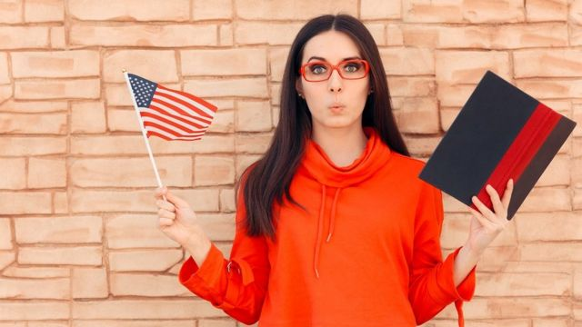 A young woman whistling, holding an American flag
