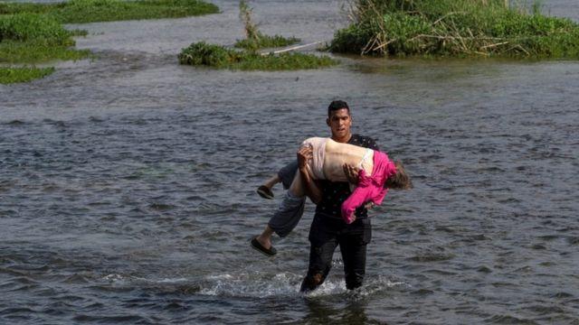 Venezuelan crossing the Rio Grande with a woman in his arms.