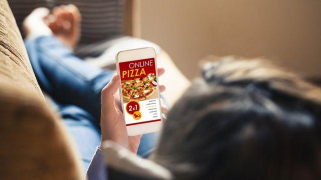 pessoa no sofá pede pizza pelo celular