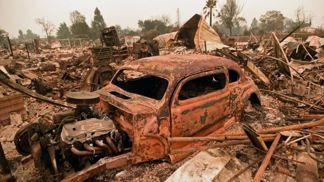 A destroyed car is seen among the ruins of a burned neighborhood after the Carr fire passed through the area of Lake Keswick Estates near Redding, California on July 28, 2018