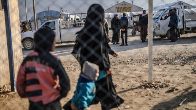 """One of the two detained French women who fled the Islamic State group""""s last pocket in Syria walks with her child after speaking to a AFP reporter at al-Hol camp in the al-Hasakeh governorate in northeastern Syria on February 17, 2019."""