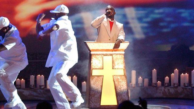 """嘻哈歌手坎耶有个绰号是""""Yeezus""""(与耶稣Jesus谐音)。上图是他在舞台上演绎嘻哈音乐作品《与耶稣同行》(Jesus Walks)时的照片。"""