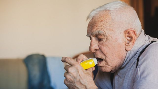 Elderly man using an inhaler