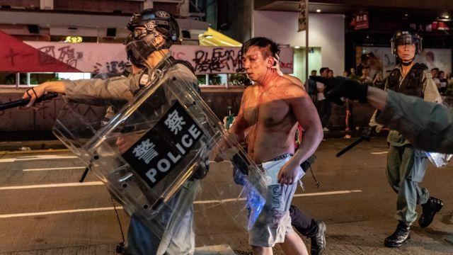 La policía escolta a un hombre que fue golpeado por los manifestantes.