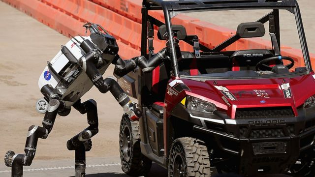 A robot climbs out of a Polaris vehicle after driving through obstacles during a show by the Pentagon's Defense Advanced Research Projects Agency (DARPA), June 2015