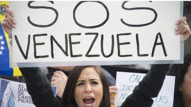 Una mujer con un cartel que dice SOS Venezuela