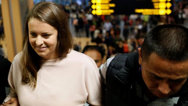 Melissa Reid of Glasgow, Scotland walks next to immigration officers before boarding a flight