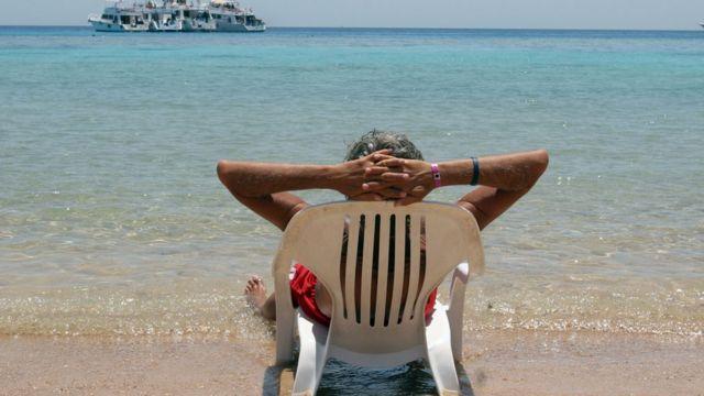 سائح ايطالي يجلس مستلقيا على أحد شواطئ منتجع شرم الشيخ المصري