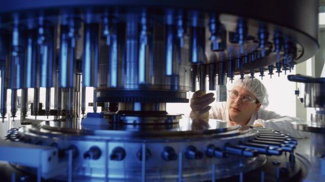 Trabalhador opera numa máquina que produz medicamentos