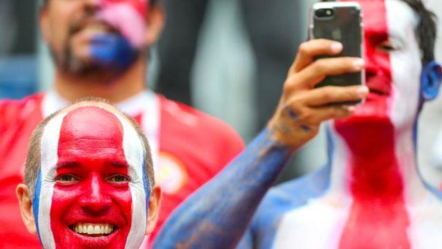 Homens com os rostos pintados com as cores da bandeira da Costa Rica, vermelho, branco e azul