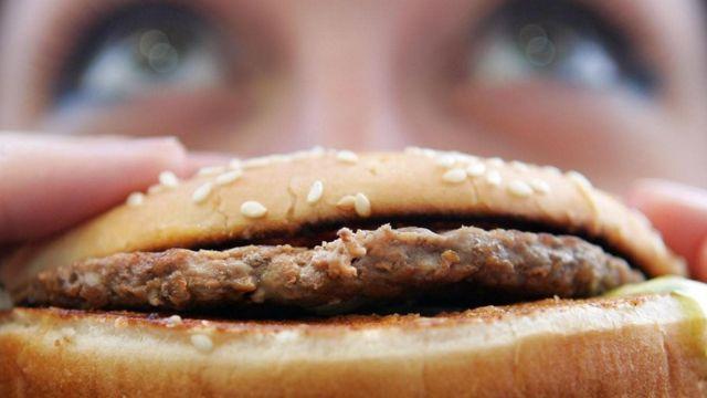 Persona comiendo hamburguesa