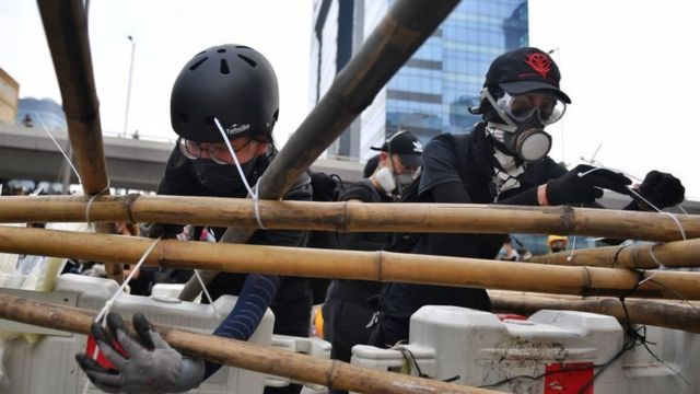 Люди в касках и респираторах связывают бамбуковые шесты