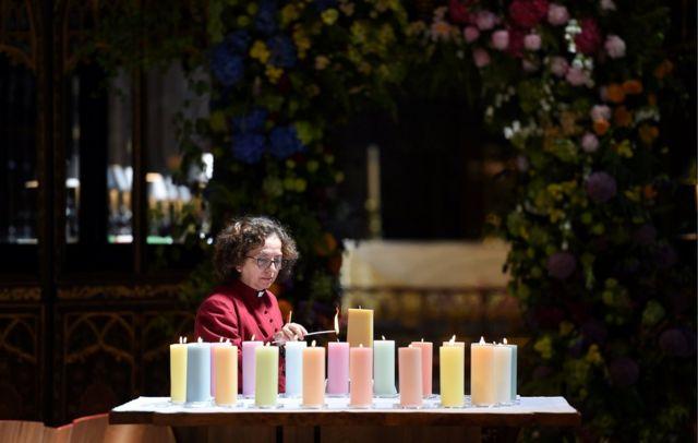 قسيسة تضيئ الشموع لضحايا هجوم مانشستر أرينا في بريطانيا، قبل خدمة في كاتدرائية مانشيستر بمناسبة مرور عام على التفجير الانتحاري الذي راح ضحيته 22 شخصا.