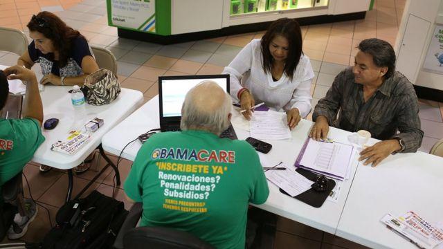ショッピングモールで保険会社から「オバマケア」について説明を受ける人々