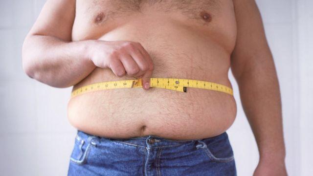 Homem medindo a circunferência da barriga