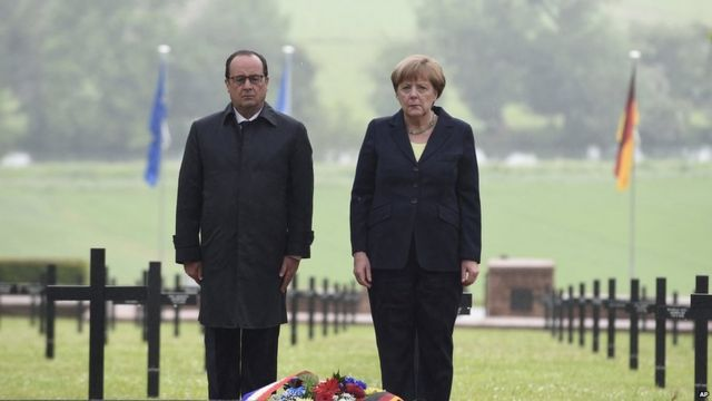 French President Francois Hollande and German Chancellor Angela Merkel pay their respects after laying a wreath.