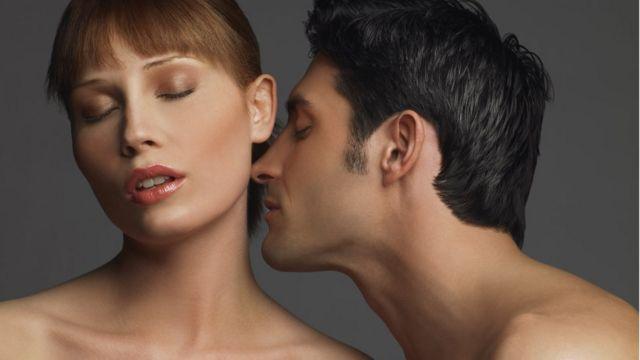 Un hombre huele el cuello de una mujer. Ambos tienen los ojos cerrados