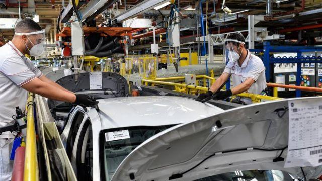 Operários trabalham em fábrica de carros