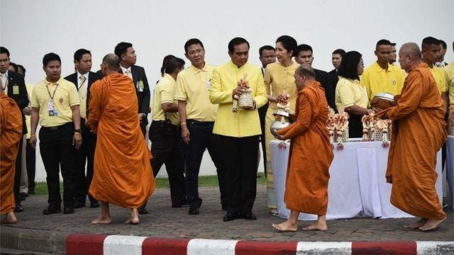 王宮前で僧侶の托鉢に施しをするプラヤット首相(9日)