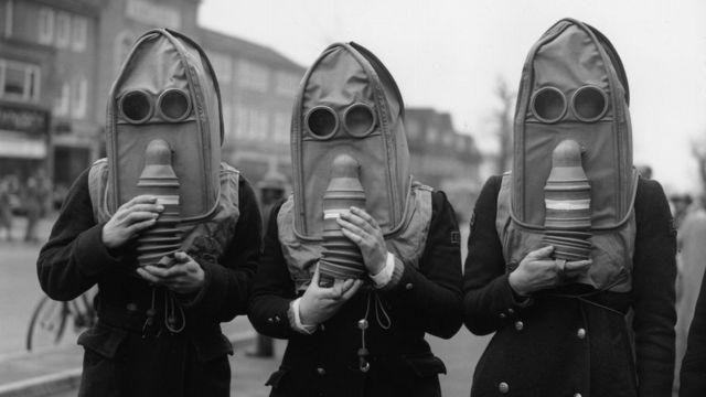 Tres personas con máscaras de gas en Reino Unido, en 1941.