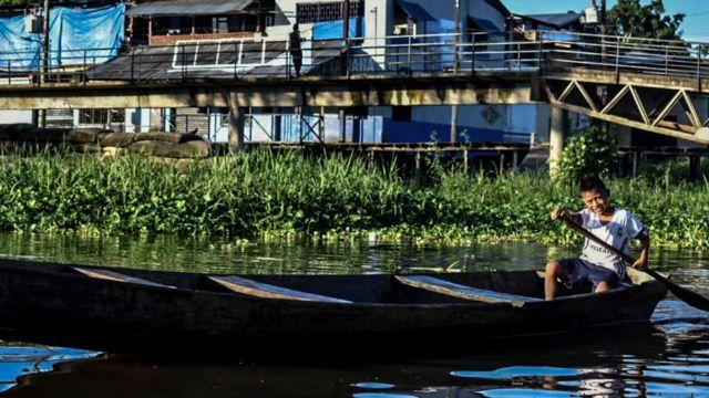 Niño navegando en bote en la Amazonía colombiana.