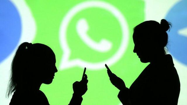 Mulheres usam o celular, com logo do WhatsApp no fundo
