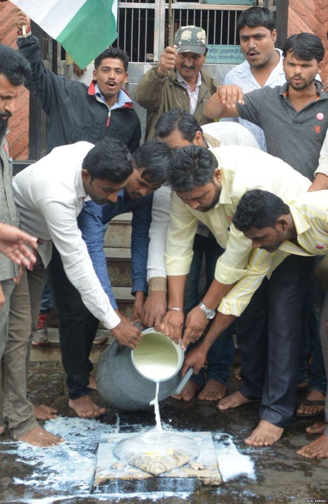 मंदिरात दूध ओतून आंदोलन करताना