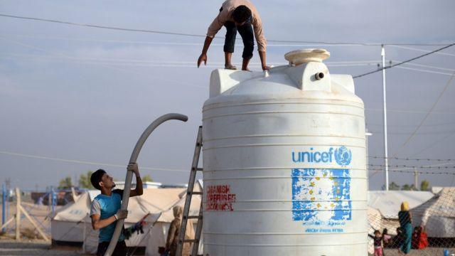 इरबिल के पास बनाए गए संयुक्त राष्ट्र के शरणार्थी शिविर में पानी की टंकी लगाते कर्मचारी.