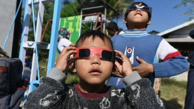 Children use special glasses to watch the eclipse in Wan Twin, Myanmar
