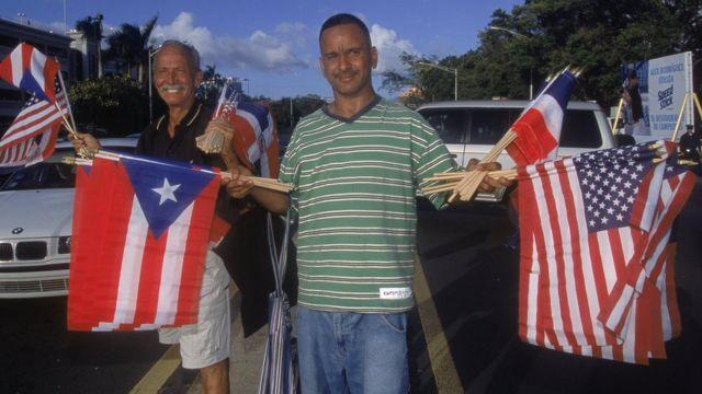 Puertorriqueños vendiendo banderas de Estados Unidos y de PR.