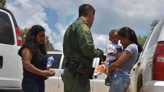 Una madre indocumentada con su hijo en brazos con un agente fronterizo de los EE.UU.